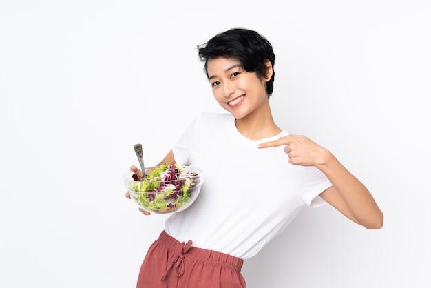 Молодая вьетнамская женщина с короткими волосами держит салат над изолированной стеной