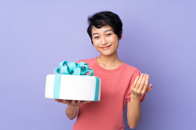 Young vietnamese woman with short hair holding a big cake over purple wall inviting to come with hand