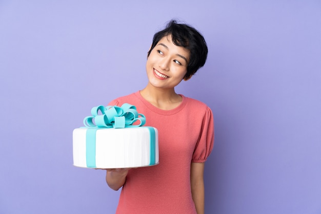 Young vietnamese woman with short hair holding a big cake over purple wall looking up while smiling
