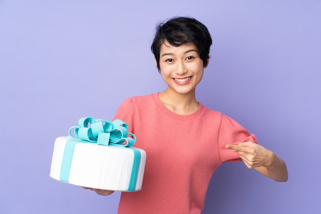 Young vietnamese woman with short hair holding a big cake over purple wall and pointing it