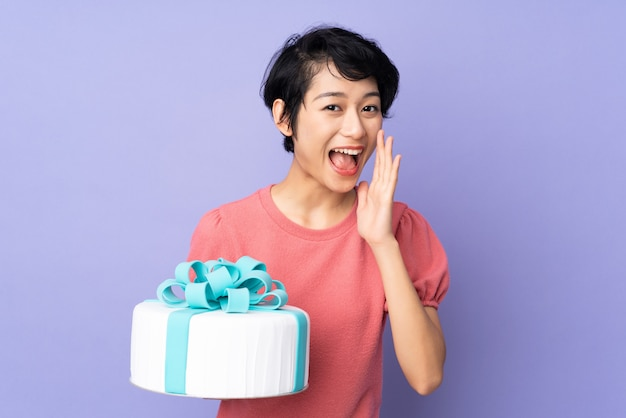 Young vietnamese woman with short hair holding a big cake over purple wall shouting with mouth wide open