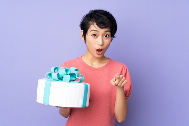 Young vietnamese woman with short hair holding a big cake over purple wall surprised and pointing front