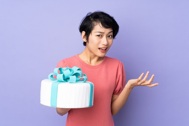 Young vietnamese woman with short hair holding a big cake over purple wall with shocked facial expression
