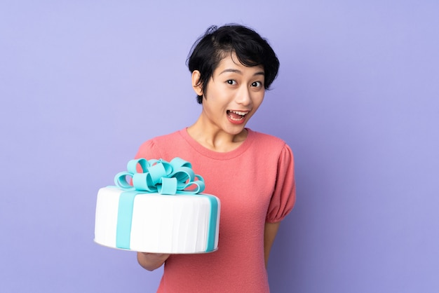 Young vietnamese woman with short hair holding a big cake over purple wall
