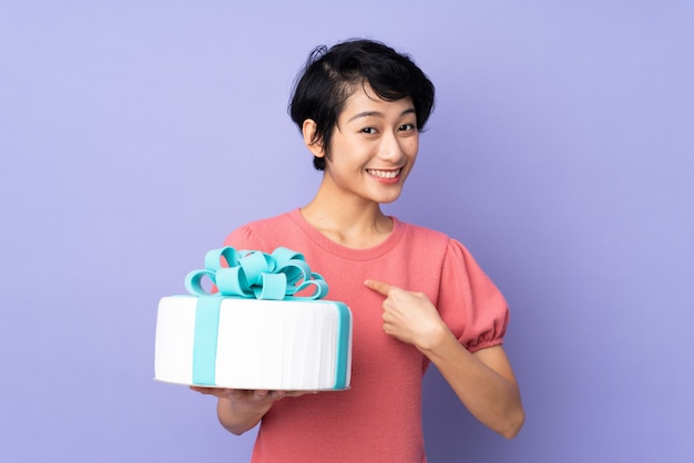 Young vietnamese woman with short hair holding a big cake
