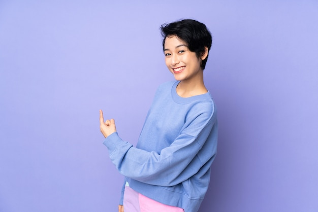 Young vietnamese woman with short hair over isolated purple wall pointing back