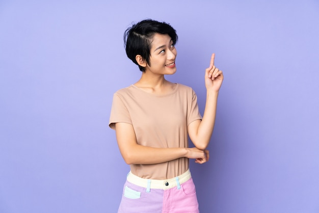 Young vietnamese woman with short hair over isolated purple wall pointing up a great idea