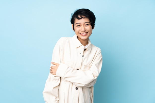Young vietnamese woman with short hair over isolated wall laughing