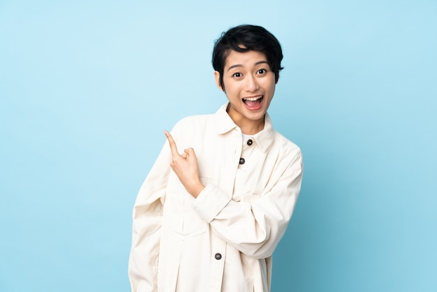 Young vietnamese woman with short hair over isolated wall surprised and pointing side