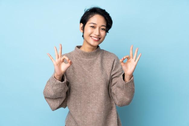 Молодая въетнамская женщина с короткими волосами над изолированной показывая одобренный знак с двумя руками