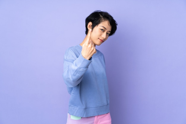 Young vietnamese woman with short hair over purple wall doing coming gesture