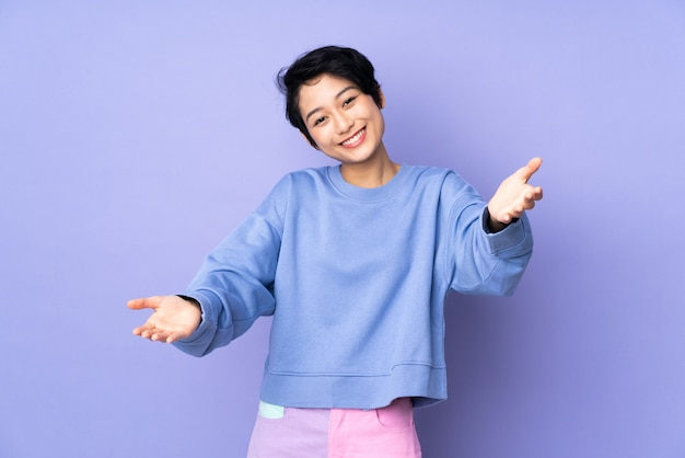 Young vietnamese woman with short hair over purple wall presenting and inviting to come with hand