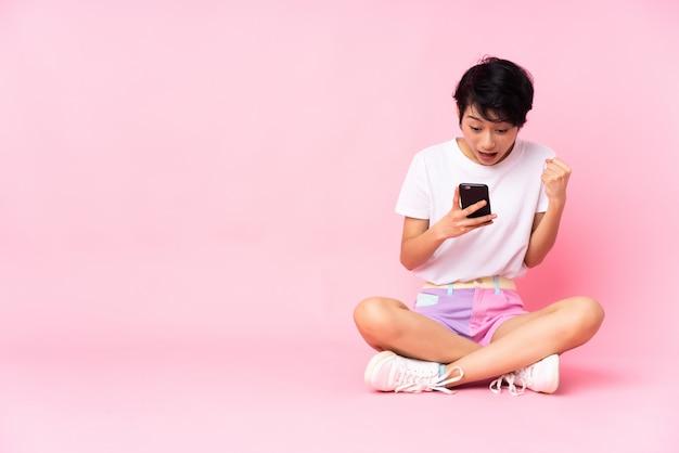 Молодая вьетнамская женщина с короткими волосами, сидящая на полу над изолированной розовой стеной, удивилась и отправила сообщение