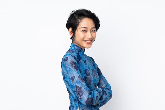 Молодая въетнамская женщина с короткими волосами нося традиционное платье над изолированной белизной смотря в сторону и усмехаясь