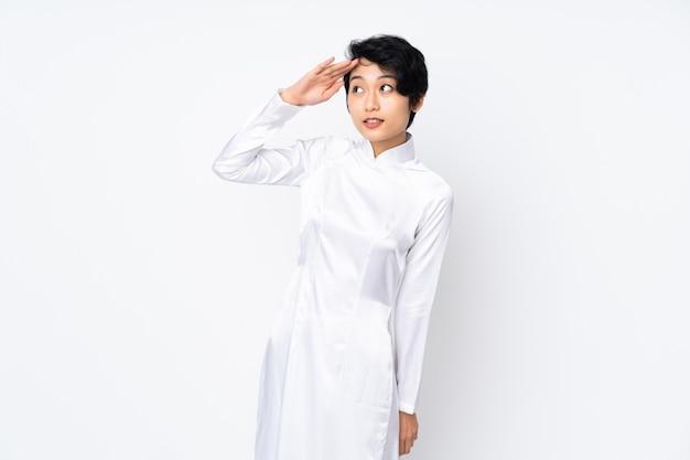 Молодая въетнамская женщина с короткими волосами нося традиционное платье над изолированной белизной салютуя с рукой с счастливым выражением