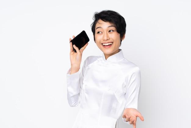Молодая вьетнамская женщина с короткими волосами в традиционном платье на белой стене ведет с кем-то разговор по мобильному телефону