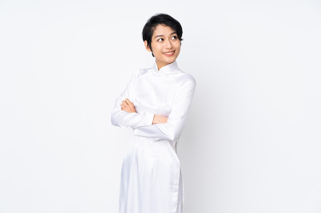 Young vietnamese woman with short hair wearing a traditional dress over white wall with arms crossed and happy