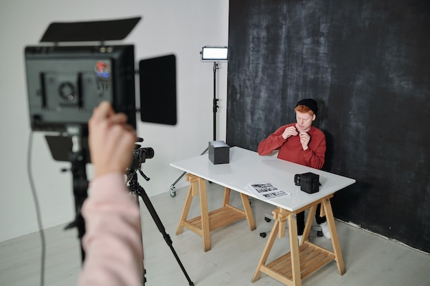 Young vlogger in casualwear sitting by desk against black background in studio and preparing for video shooting