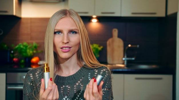 Молодой влогер нюхает духи. красивая молодая женщина распыляет и нюхает приятный парфюм во время съемки видео для бьюти-видеоблога у себя дома.