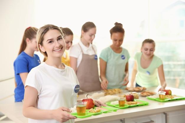 若いボランティアと彼女のチームは、屋内でさまざまな製品をテーブルの近くに置いています