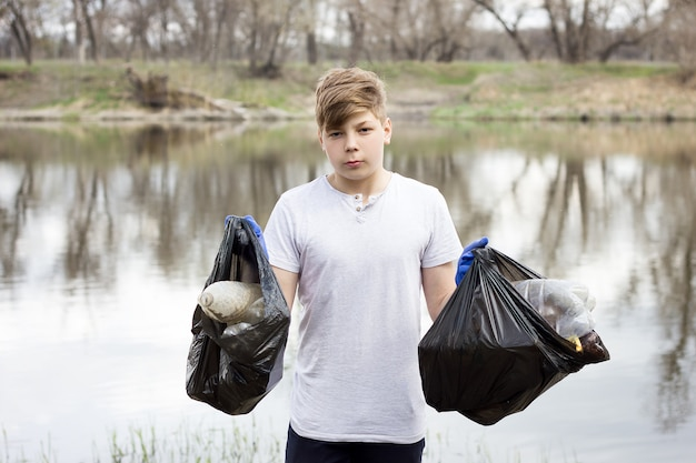 Young volunteer guy picks up trash on the banks of the spring river.