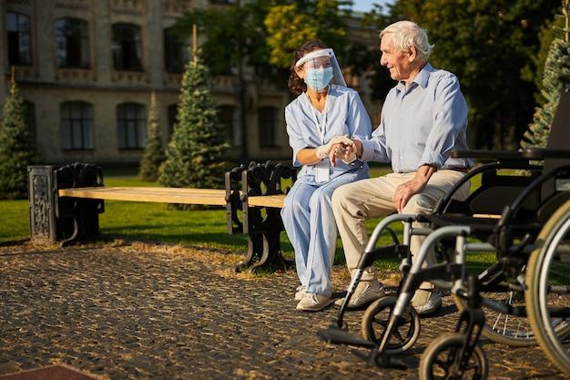 야외에서 웃는 노인의 손을 잡고 젊은 자원 봉사자