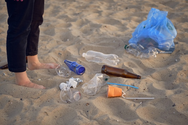 Young volunteer is walking with garbage bag along a dirty beach of the river and cleaning up trash
