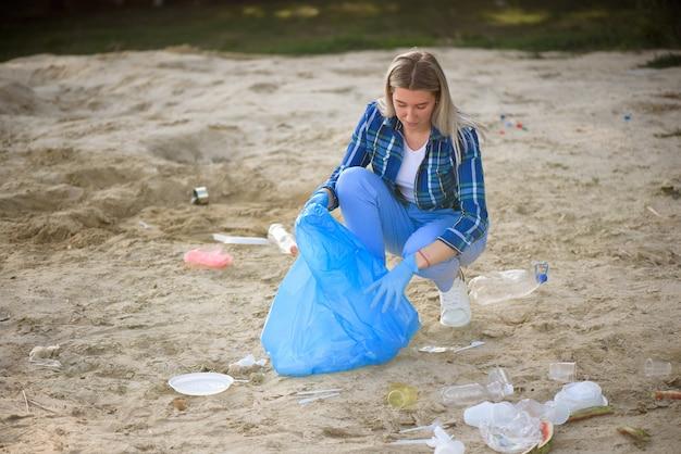 Молодой волонтер собирает пластиковые бутылки на пляже возле парка.