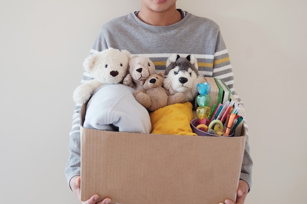 Young volunteer preteen teenage boy holding a box full of used toys