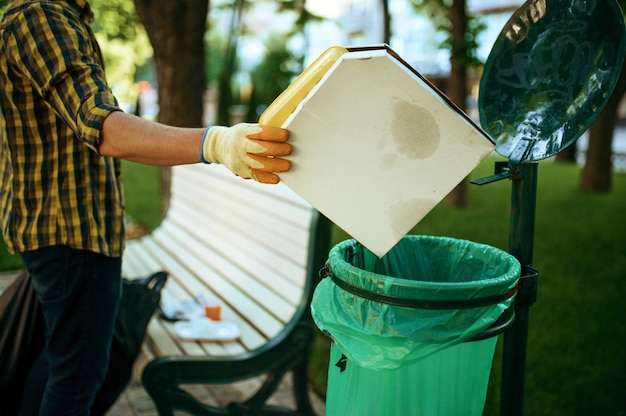 Young volunteer puts trash in plastic bag in park, volunteering. male person cleans forest, ecological restoration, eco lifestyle, garbage collection and recycling, ecology care, environment cleaning