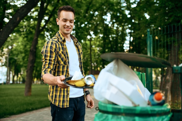 Young volunteer puts trash in plastic bin in park, volunteering