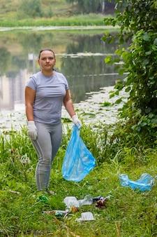 若いボランティアの女性が公園の埋め立て地でゴミを片付けます。縦の写真