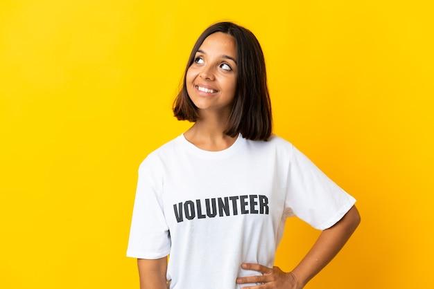 見上げながらアイデアを考えて黄色の背景に孤立した若いボランティアの女性