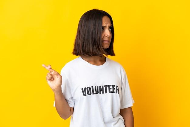 손가락을 건너고 최고를 바라는 노란색 벽에 고립 된 젊은 자원 봉사 여성