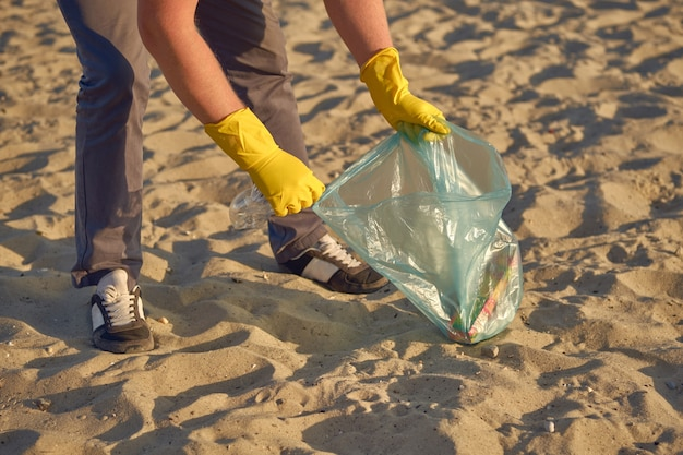 Young volunteer in yellow gloves is walking with garbage bag along a dirty beach of the river