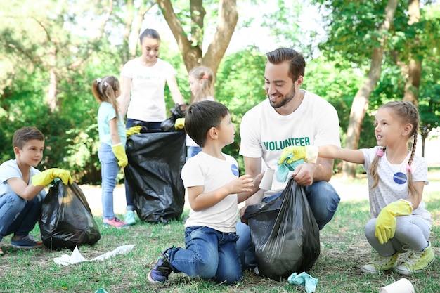 公園でゴミを収集する若いボランティアと子供たち