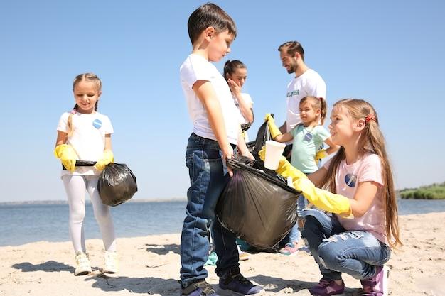 ビーチでゴミを収集する若いボランティアと子供たち