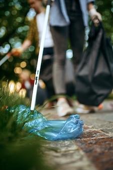 Молодые волонтеры собирают мусор в полиэтиленовых пакетах в парке, волонтерство