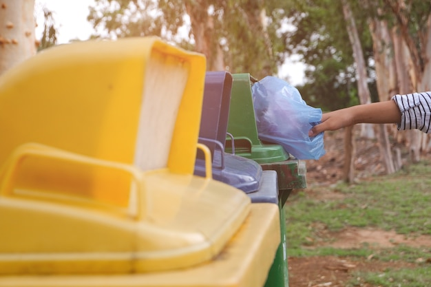 Young volunteers throw waste into the bucket, people and ecology. volunteer concept.