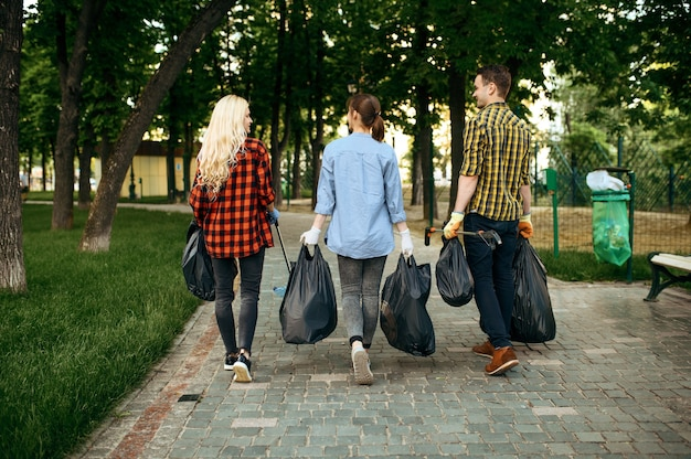 Young volunteers with plastic trash bags in park, volunteering. male person cleans forest, ecological restoration, eco lifestyle, garbage collection and recycling, ecology care, environment cleaning