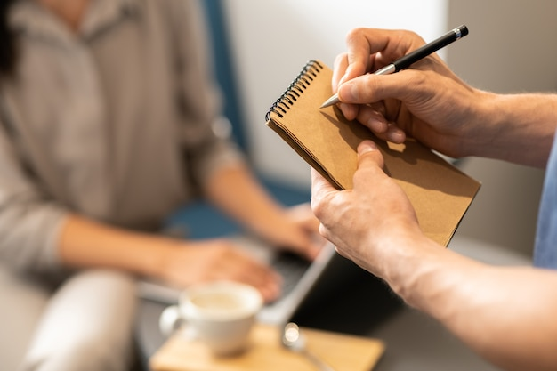 クライアントの順序を書き留めようとしている間、空白のページの上にメモ帳とペンを持っている若いウェイター