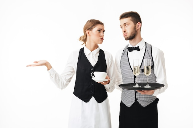 Young waiter holding tray with glasses of champagne and sad waitress holding cup of coffee in hands while tiredly