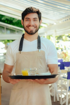 Young waiter holding tray.
