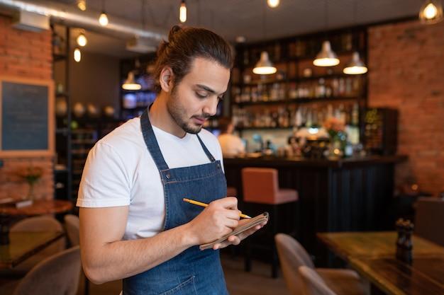 Молодой официант в синем фартуке и белой футболке записывает заказ одного из клиентов в блокноте, стоя в кафе или ресторане