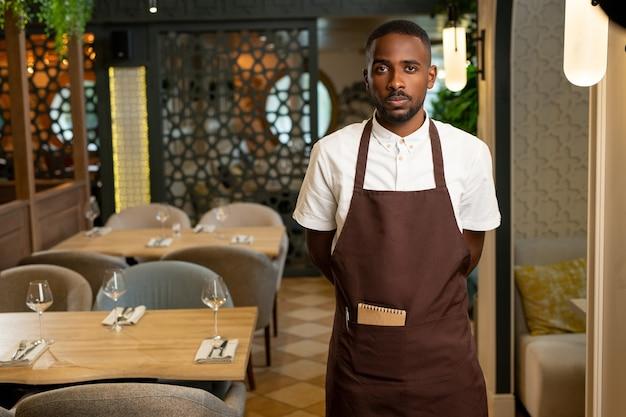 Молодой официант в коричневой форме стоит в проходе между столиками, обслуживаемыми для гостей кафе или ресторана