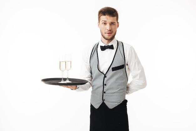 思慮深くしながらシャンパンのグラスと制服の保持トレイに若いウェイター