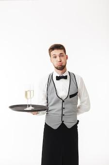 疲れている間シャンパンのグラスと均一な保持トレイの若いウェイター