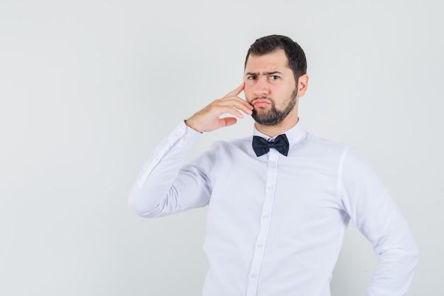 白いシャツを着た若いウェイターは、思考ポーズで立って、厳格な正面図を探しています。