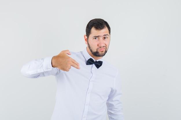 鉄砲のジェスチャーのサインを作る若いウェイターは、白いシャツを着て自分を指さし、自信を持って見えました。正面図。