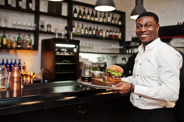 Young waiter man holds tray with burger at bar of restaurant